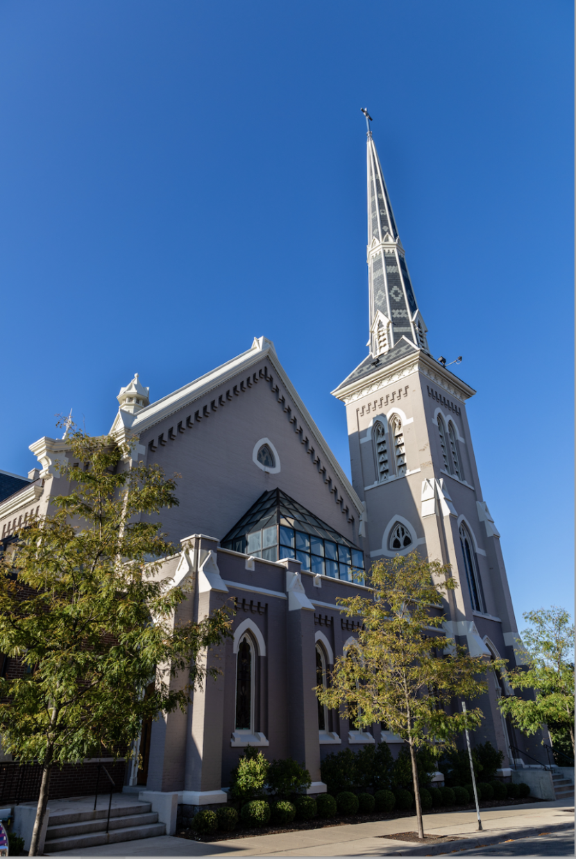 a photo of the Westminster Presbyterian Church in GR. The grey stones of the building look nice against a vibrant blue sky, and the trees are green.